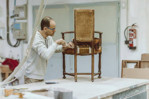 Expertise restoring wood chair while standing at workshop - OCAF00553