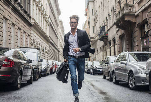 Young man running with briefcase on street in city - AJOF00828