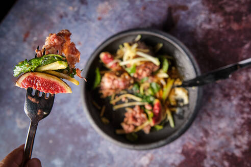 Top view of savory pig trotter with fruits and vegetables on fork in luxury restaurant on black background - ADSF18495