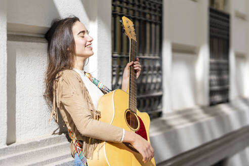 Smiling female musician playing guitar in city on sunny day - GGGF00268
