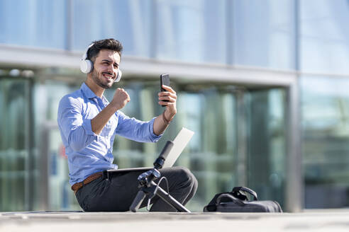 Smiling businessman wearing headphones showing winning gesture while sitting with laptop and mobile phone outdoors - GGGF00355