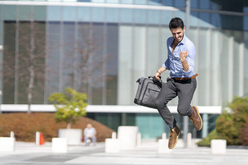 Young excited businessman holding briefcase while jumping outdoors - GGGF00373