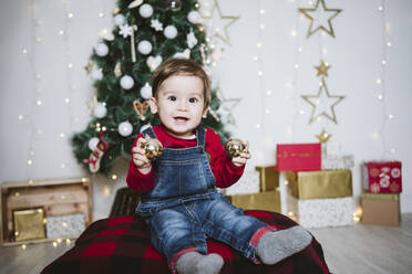 Happy baby boy playing with bauble while sitting at home during Christmas - EBBF01697