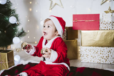 Playful baby boy in Santa Claus costume playing with bauble while sitting on blanket at home during Christmas - EBBF01703