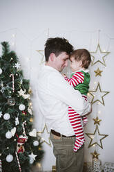 Father embracing son wearing elf costume while standing at home during Christmas - EBBF01712