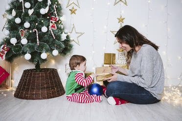 Woman giving gift to baby boy while sitting at home during Christmas - EBBF01715
