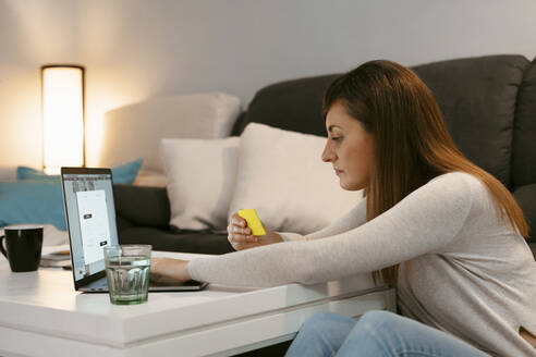 Mid adult woman with credit card shopping online on laptop while sitting at home - ERRF04779