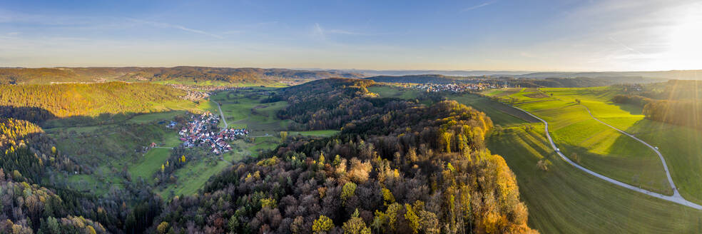 Drone view of village surrounded by autumn forest at sunrise - STSF02697
