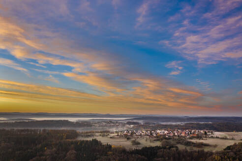 Drone view of moody sky over countryside village at foggy autumn dawn - STSF02703
