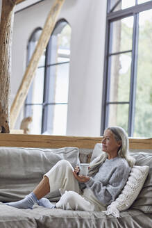 Thoughtful mature woman looking away while holding coffee cup at home - MCF01514
