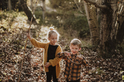 Girl and boy playing with stick and rope while standing in forest during autumn - GMLF00884