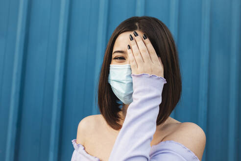 Young woman wearing face mask covering eye with hand while standing against blue wall - MIMFF00295