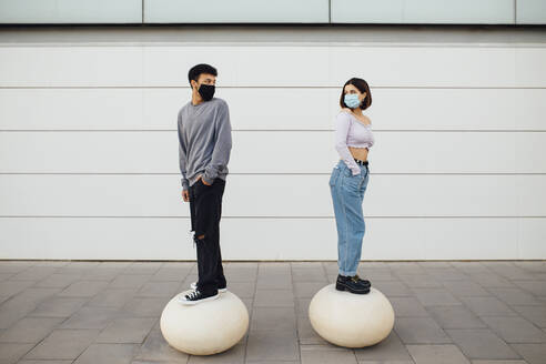 Couple with face mask looking over shoulder while standing on white concrete ball - MIMFF00301