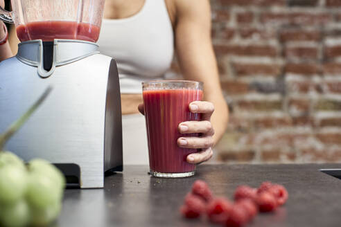 Mature woman holding glass of raspberry smoothie by blender on kitchen island - VEGF03301
