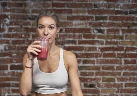 Mature woman drinking fruit smoothie against brick wall in kitchen - VEGF03304