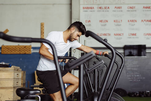 Young sportsman exercising on airbike at gym - MARF00010