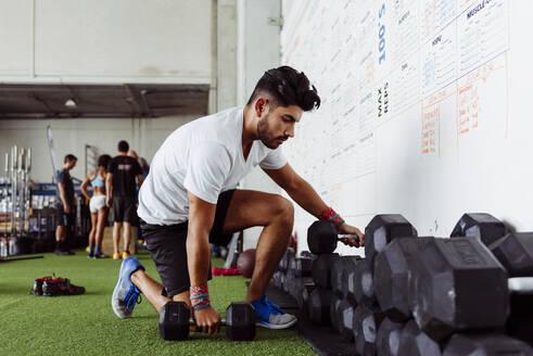 Athlete taking dumbbells at gym - MARF00016