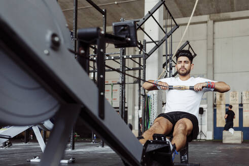 Sportsman exercising with rowing machine at gym - MARF00019