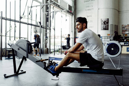 Sportsman looking away while sitting on rowing machine - MARF00022