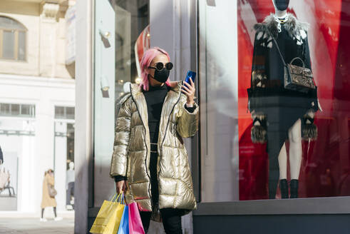 Fashionable woman with face mask carrying shopping bags while using mobile phone standing by store window - MARF00025