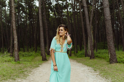 Smiling woman standing with hand in hair on forest path - MARF00030
