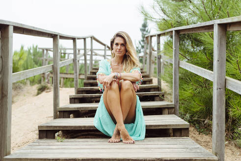 Mid adult woman sitting with legs crossed at ankle on steps at forest - MARF00033