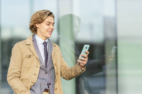 Smiling businessman using mobile phone while leaning on glass wall - GGGF00431