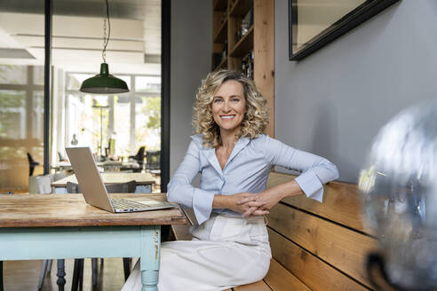 Happy businesswoman sitting with laptop in office cafeteria - PESF02424