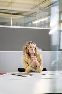 Thoughtful businesswoman smiling while leaning on desk at work pace - PESF02445