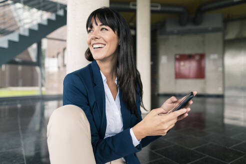 Smiling businesswoman looking away while holding smart phone in office - JOSEF02513