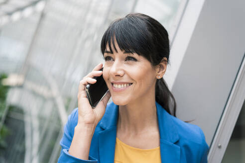 Smiling businesswoman talking on mobile phone in office - JOSEF02600