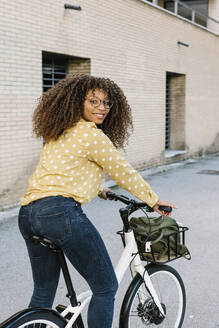 Young woman smiling while standing with bicycle on road - XLGF00785