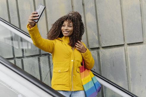 Young woman taking selfie through mobile phone while standing on escalator - JCZF00344