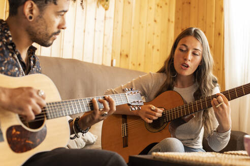 Woman singing while playing guitar with man at home - LJF01879