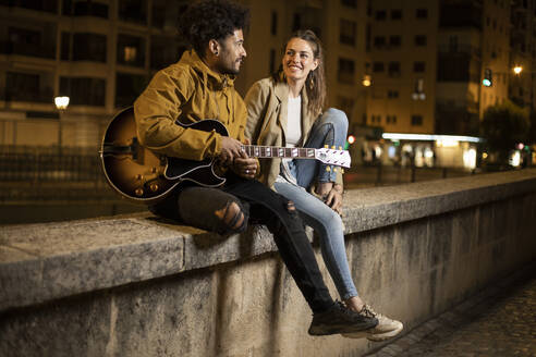 Couple with guitar smiling while sitting on retaining wall - LJF01921