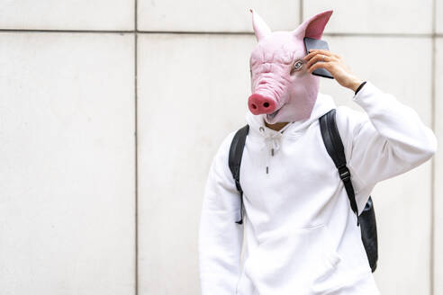 Young man with pig mask taking on mobile phone against wall - GGGF00455