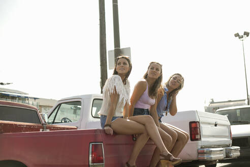 Carefree friends sitting on edge of truck during summer vacation - AJOF00960