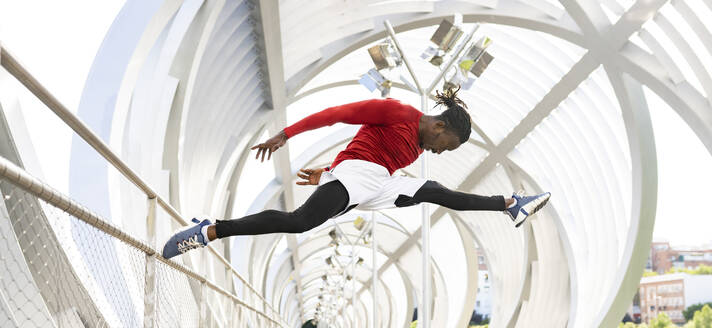 Acrobat jumping while exercising on walkway - JCCMF00141