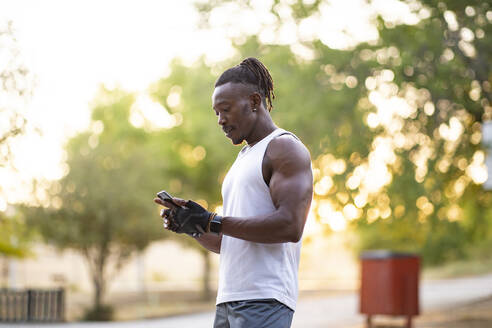 Sportsman using mobile phone while standing outdoors - JCCMF00177