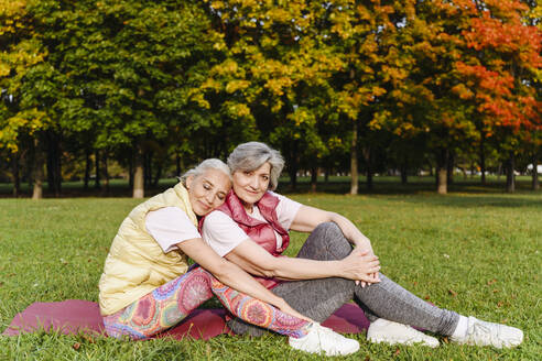 Mature woman resting with eyes closed on female friends shoulder at public park - VYF00367