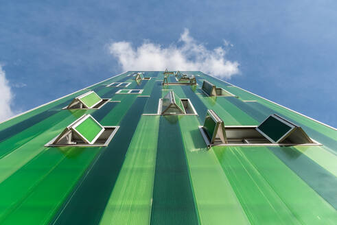 From below contemporary building with vivid green facade and opened windows on blue sky - ADSF19197