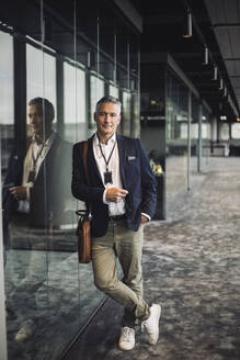 Portrait of entrepreneur in businesswear standing at workplace - MASF20958