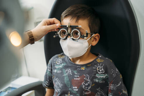 Boy wearing eyeglasses for medical eye test in clinic during COVID-19 - MPPF01313