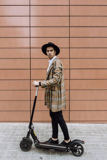 Stylish young man wearing checked jacket and hat standing with push scooter in city - XLGF00880