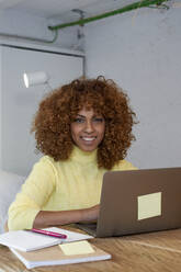 Smiling woman with laptop at home - VEGF03306