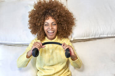 Laughing woman playing with headphones after work in bedroom - VEGF03318