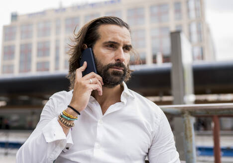 Candid portrait of bearded businessman sitting outdoors and talking on smart phone - JCCMF00197