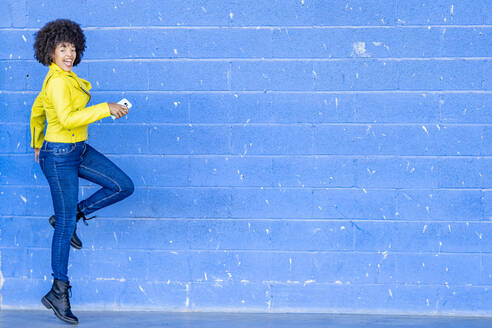 Cheerful young woman with mobile phone dancing against blue wall - GGGF00491