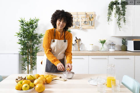 Smiling woman squeezing orange in bowl while standing at kitchen - GIOF10042