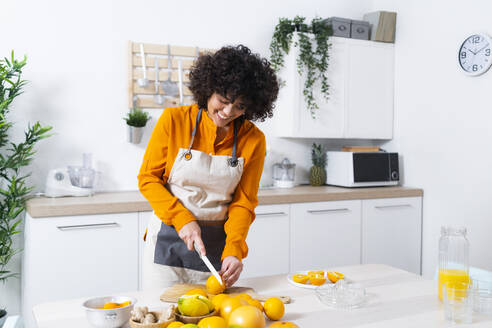 Woman smiling while cutting orange standing in kitchen at home - GIOF10045